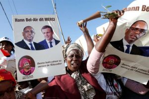 Supporters hold boards with pictures of Senegalese President Macky Sall and French President Emmanuel Macron prior to the inauguration of a college in Dakar, on February 2, 2018.  / AFP PHOTO / POOL / PHILIPPE WOJAZER